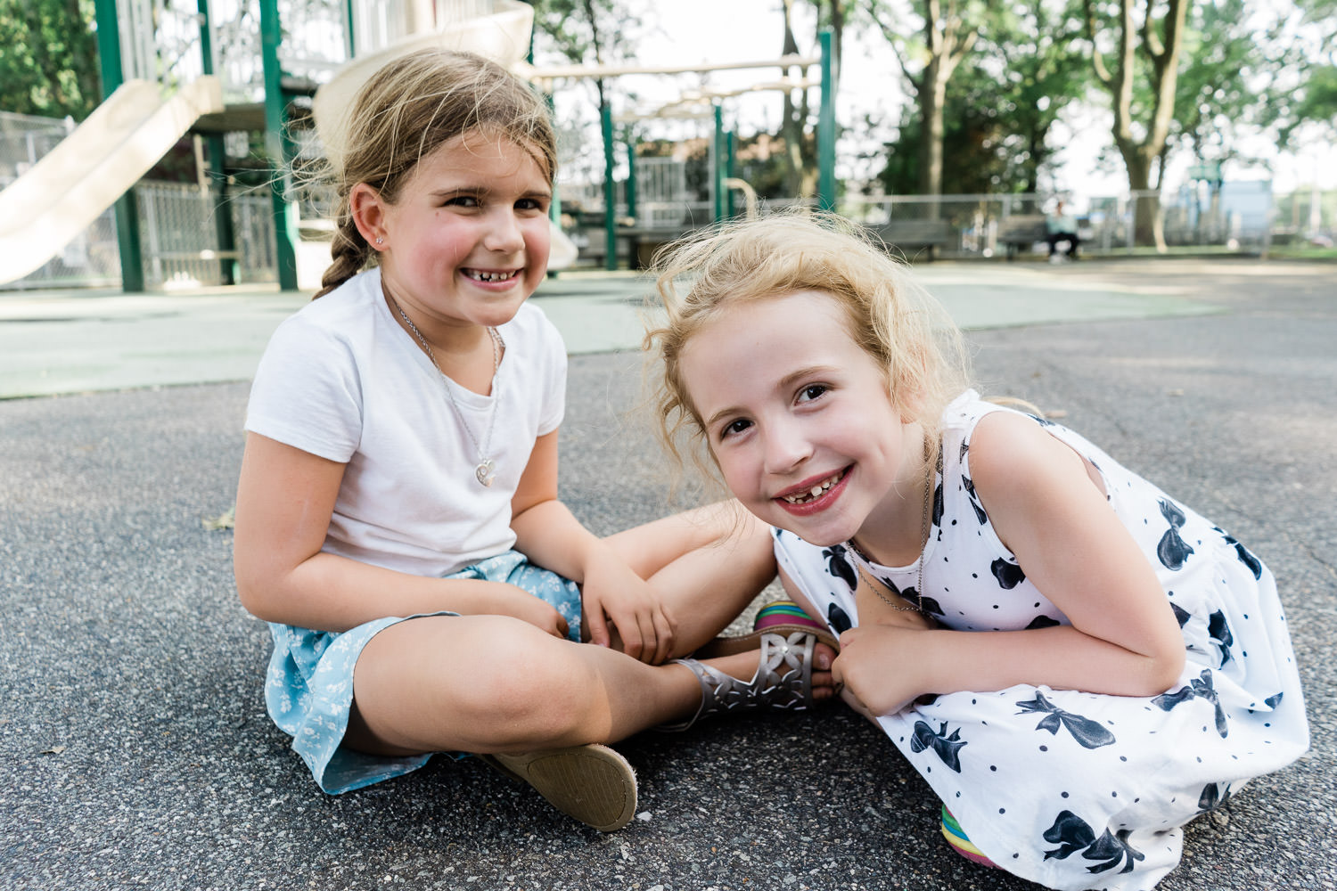 Two little girls sit on the ground at a town park.