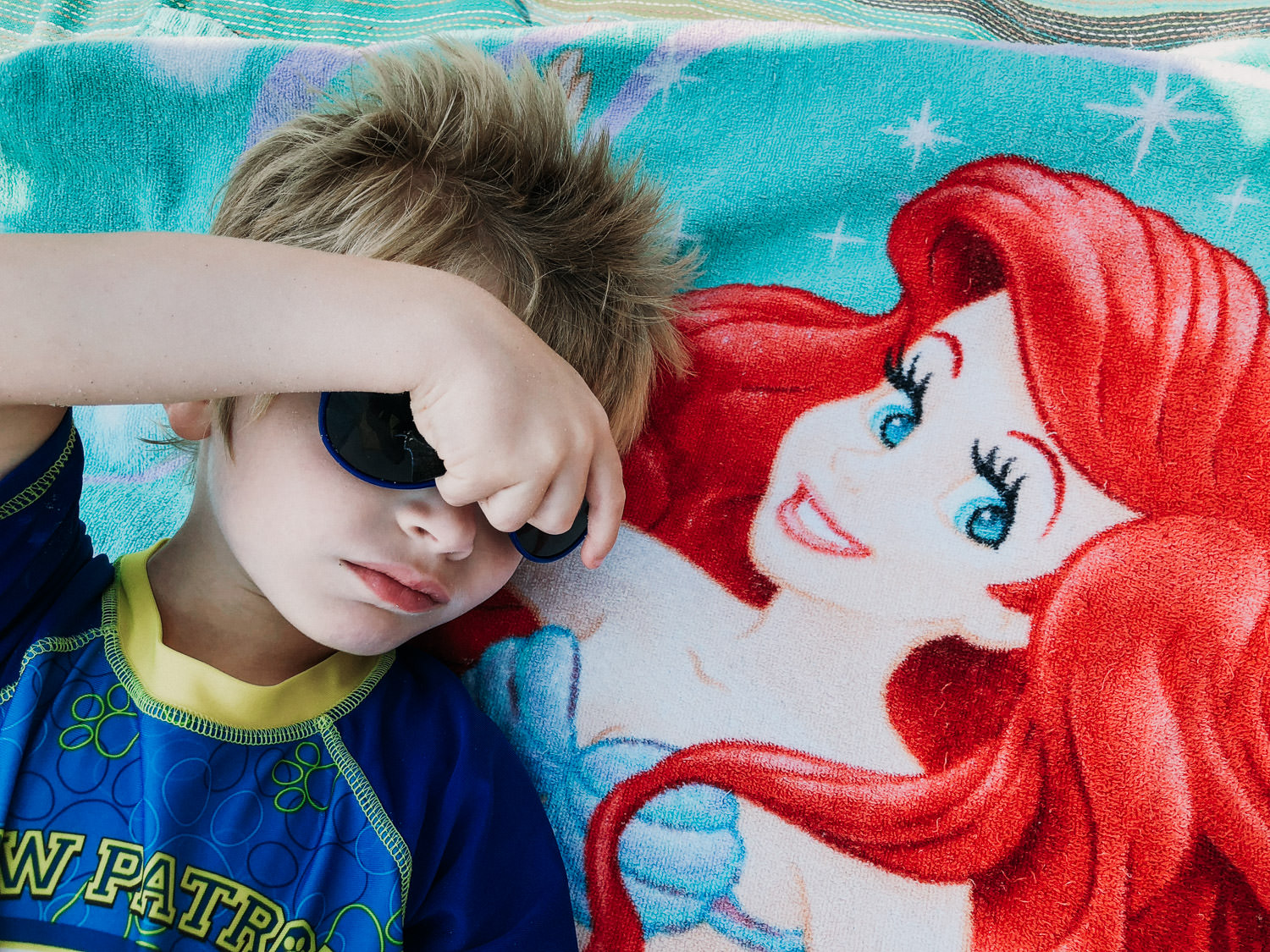 "A little boy lies down on a towel with ""The Little Mermaid"" on it."