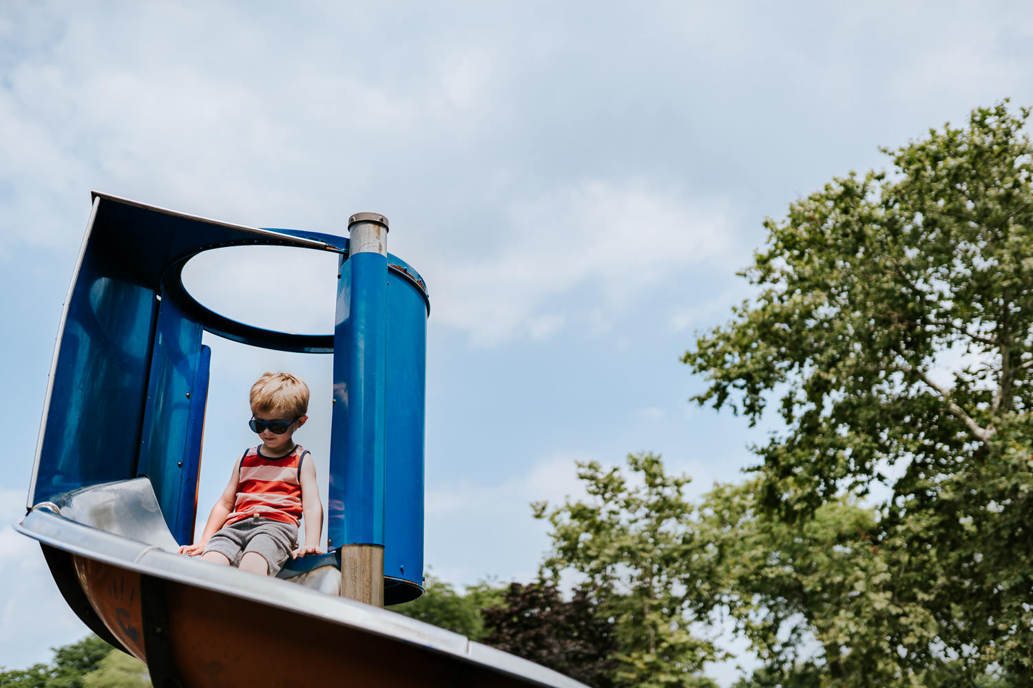 A little boy perches at the top of a slide.