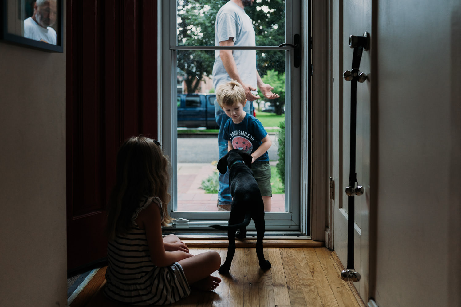 A dog looks at a little boy at the front door.