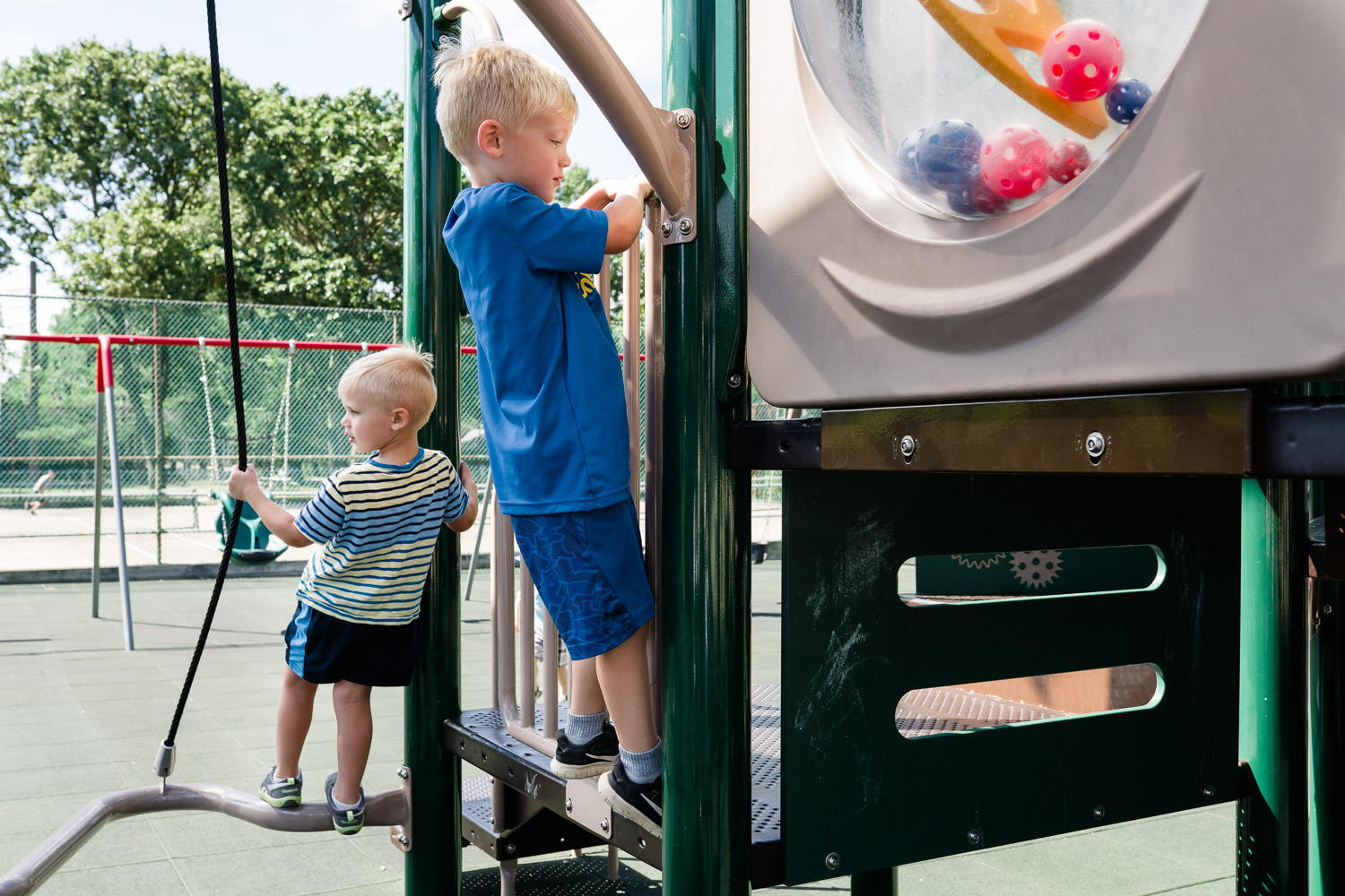 Two little boys play on a playground structure.