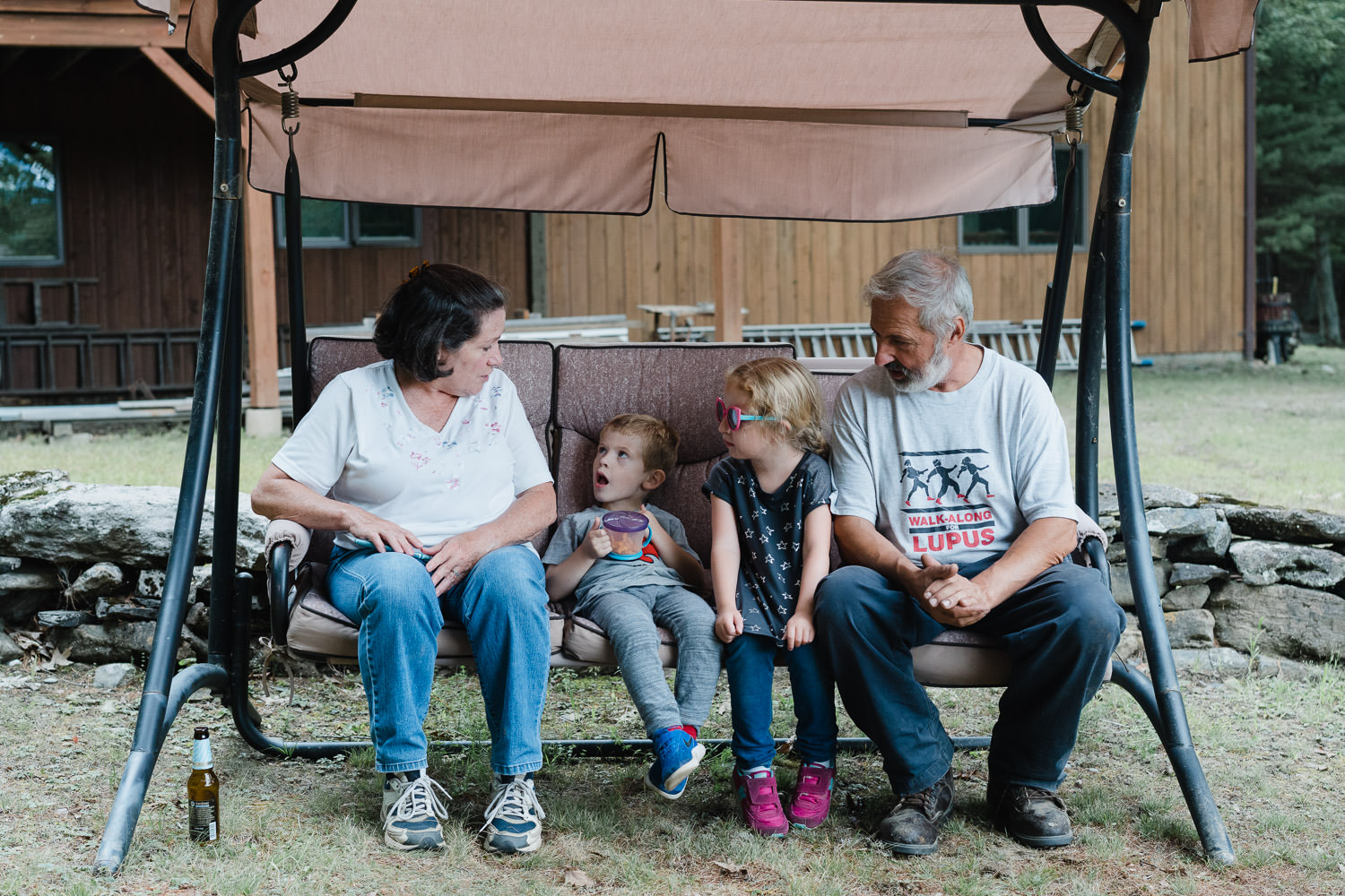A family sits in a recliner swing on their lawn.