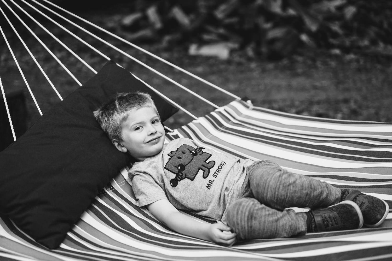 A little boy lies in the hammock.