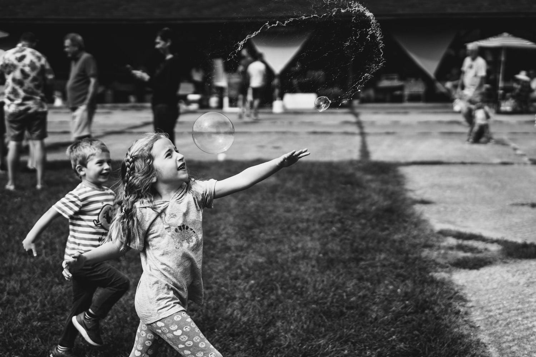 A little girl pops a bubble.