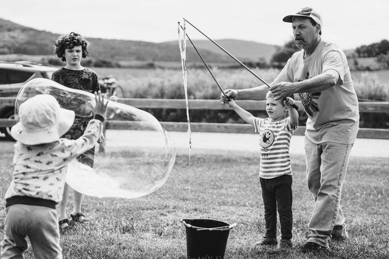 A little boy makes bubbles.