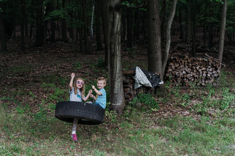Two kids swing in a tire swing.