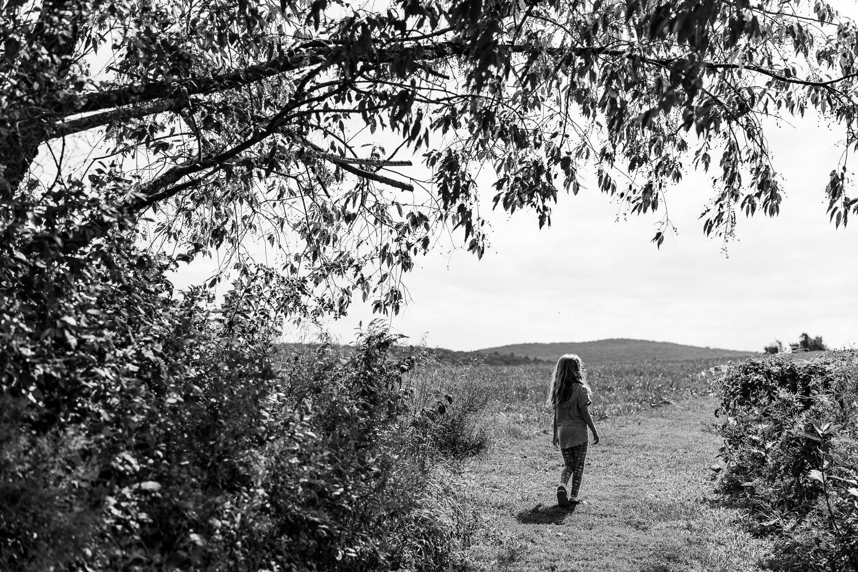A little girl walks under a tree.