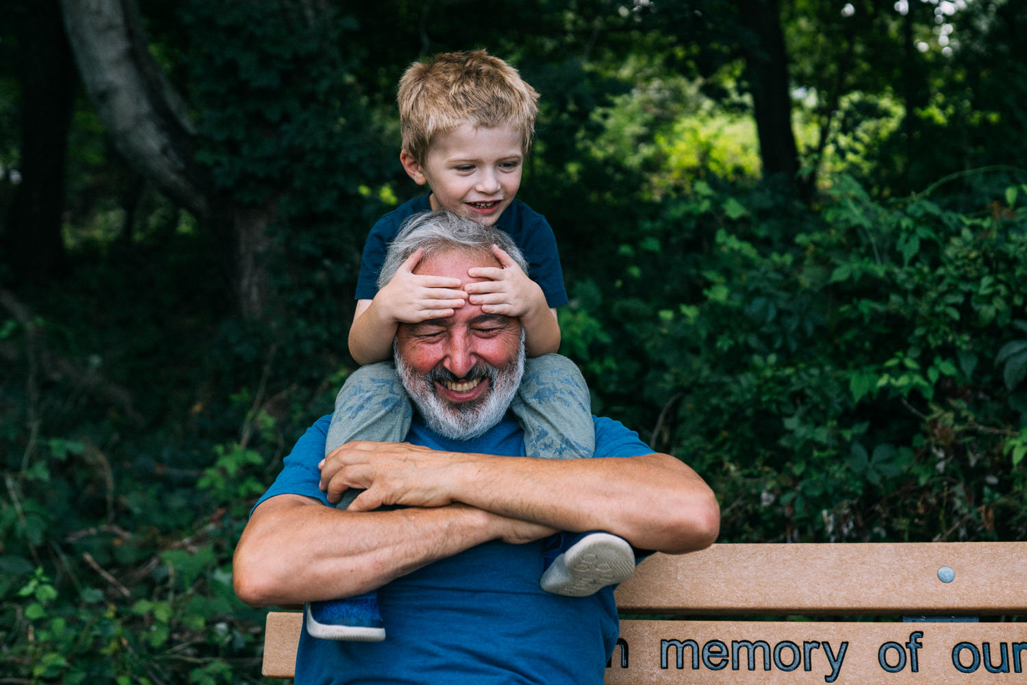 A little boy sits on his grandfather's shoulders.