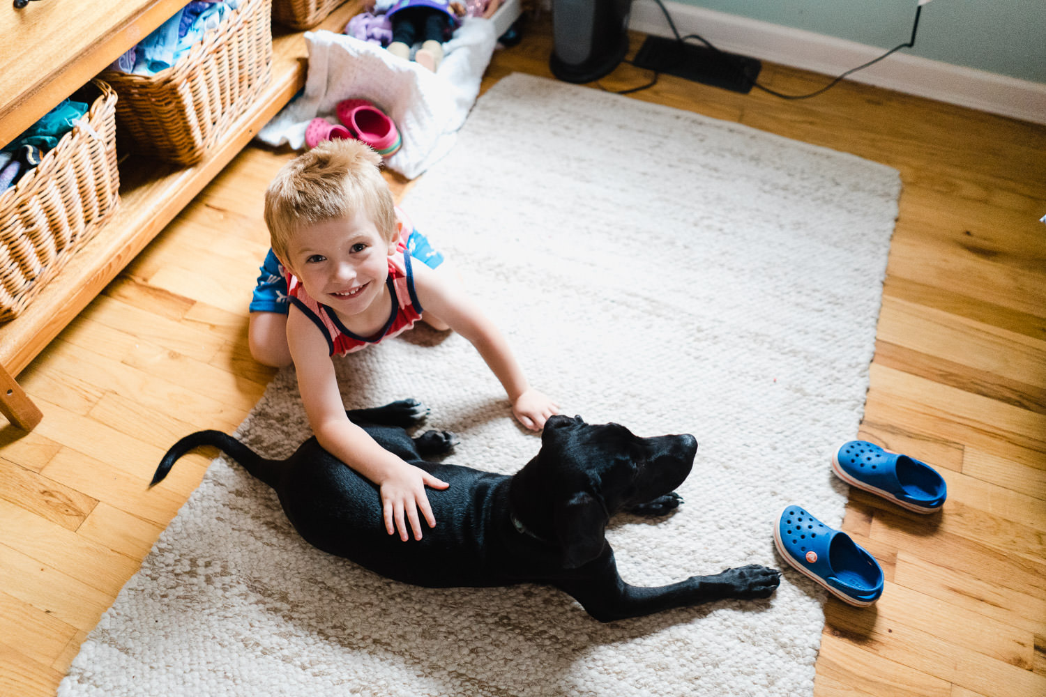 A little boy pets his dog on the floor of his room.