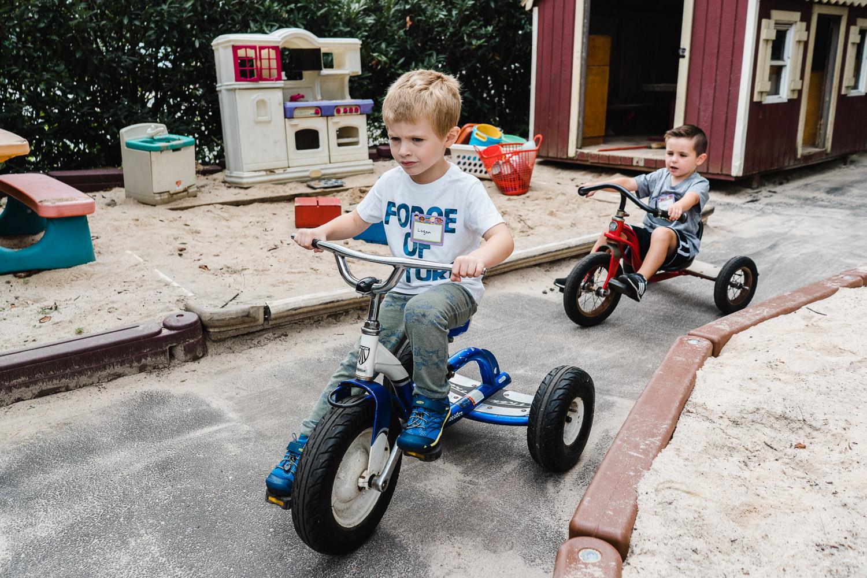 Preschoolers ride tricycles at school.