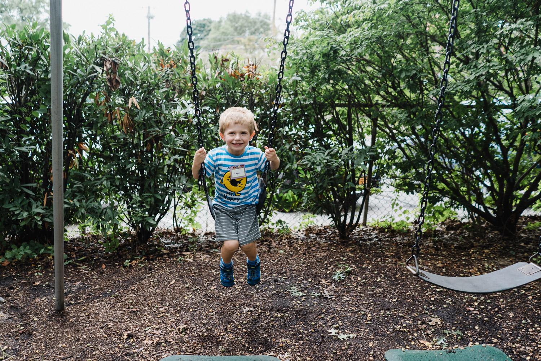 A little boy swings on a swing.