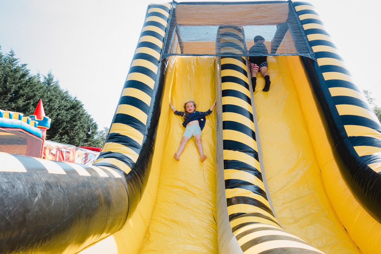 A little girl flies down a slide.