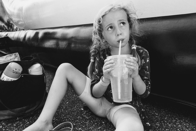 A little girl drinks a big lemonade.