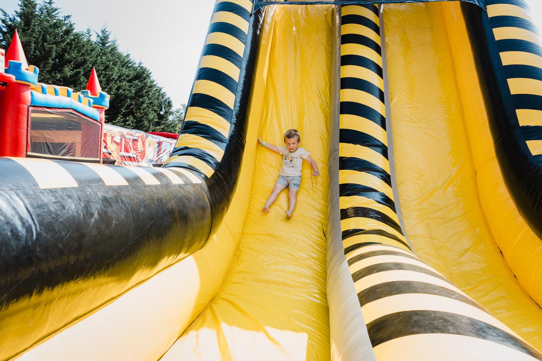 A little boy flies down a tall slide.