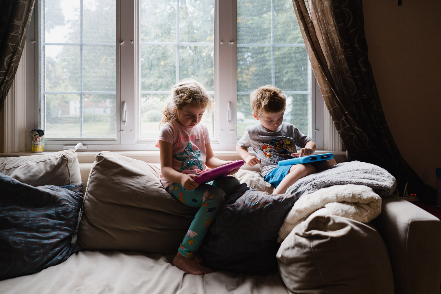 Two children play with tablets on a couch.