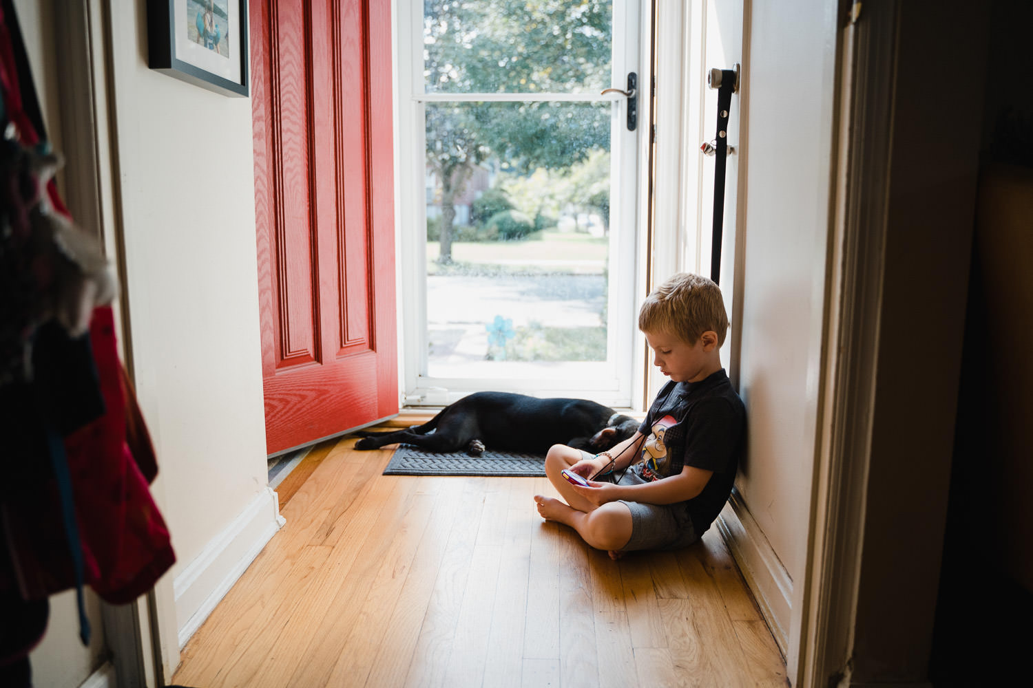 A boy and his dog sit near their front door.