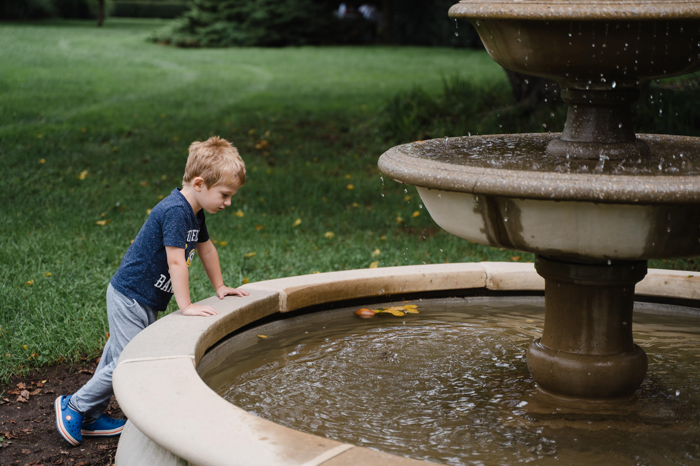 A little boy looks into a fountain.