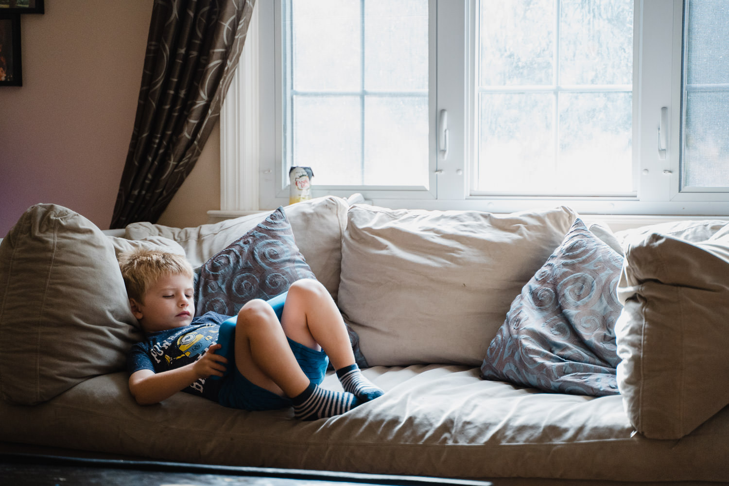 A little boy plays with a tablet on his couch.