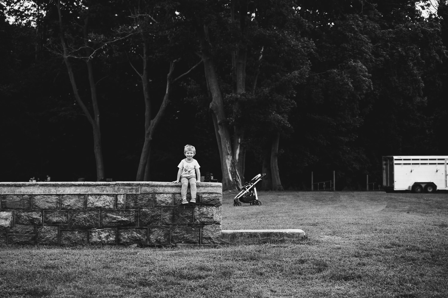 A little boy perches on a wall at Sands Point.
