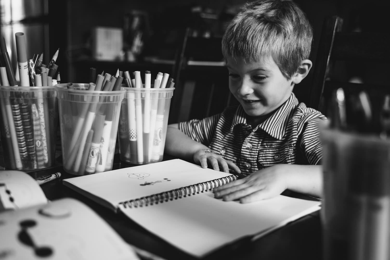 A little boy colors a picture.
