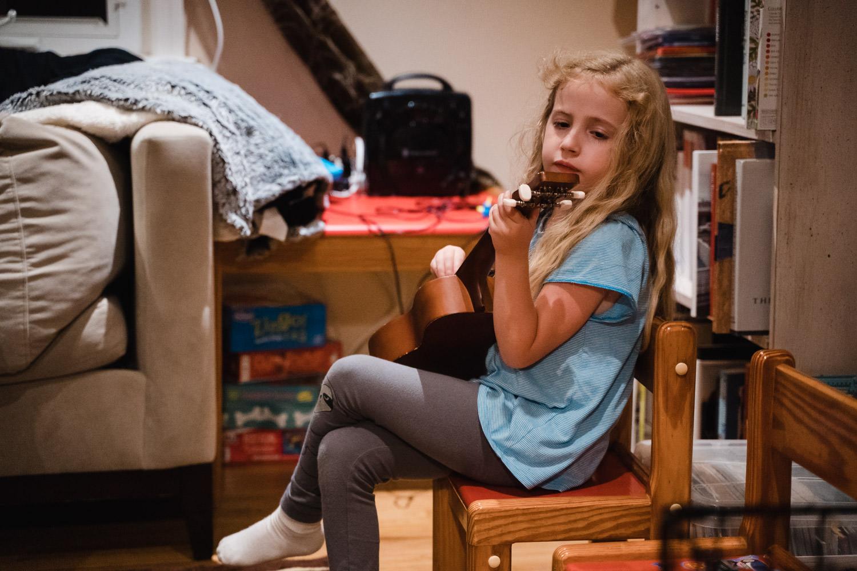 A little girl plays a ukelele.