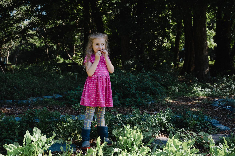 A little girl eats greens at Restoration Farm.