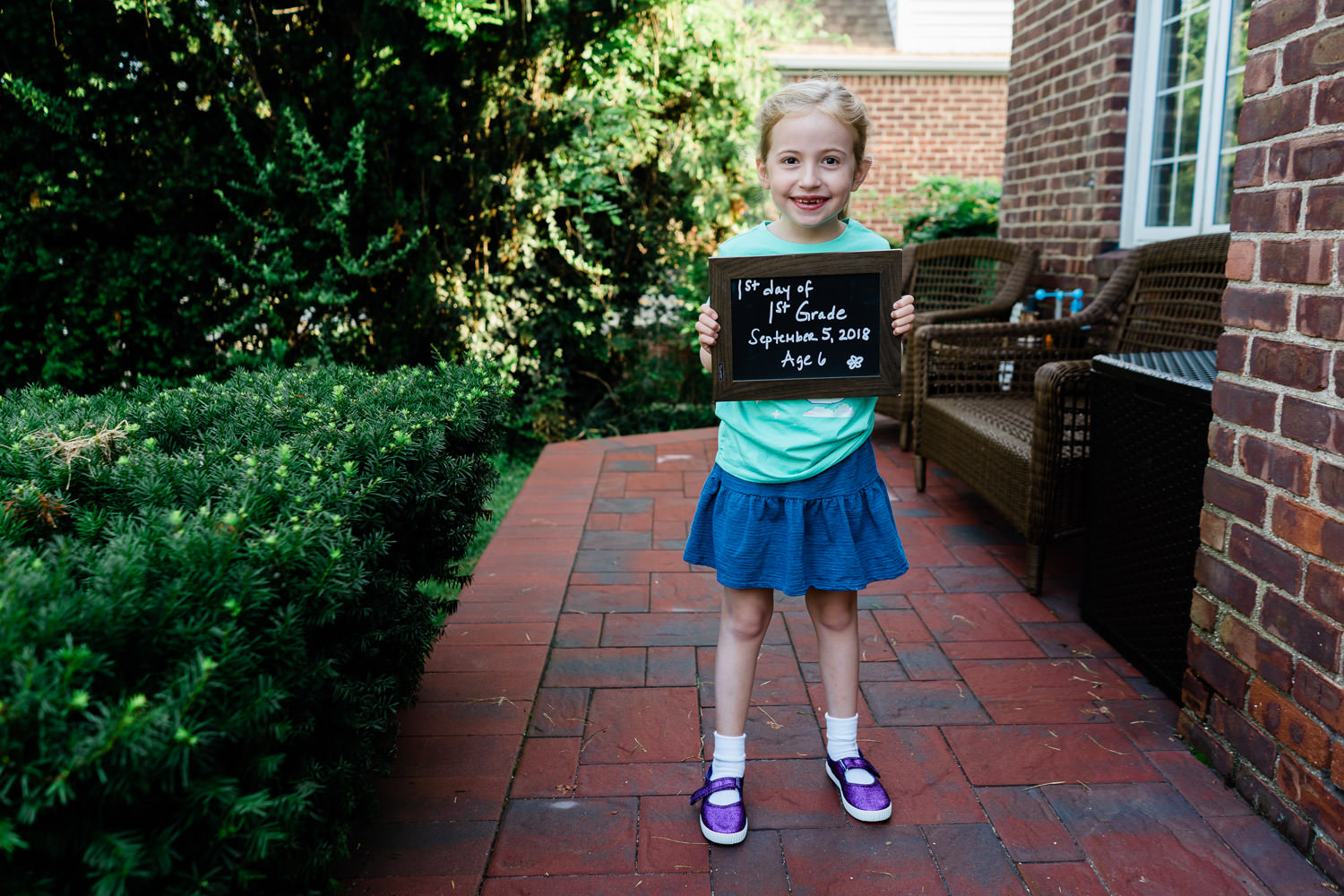 A little girl poses with a sign on the first day of 1st grade.