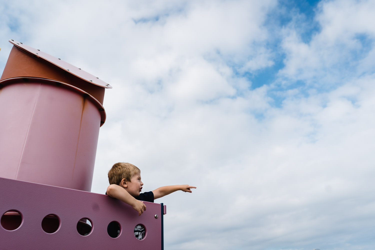 A little boy plays in a boat play structure at Captree State Par