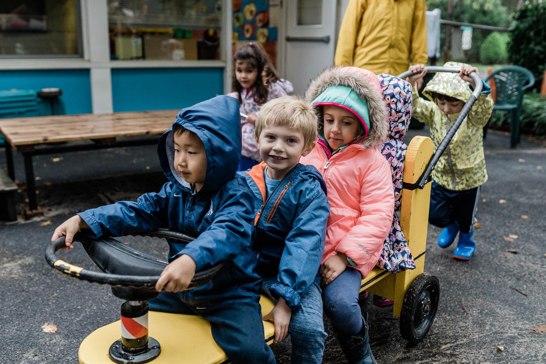 Preschoolers ride on a wagon at school.