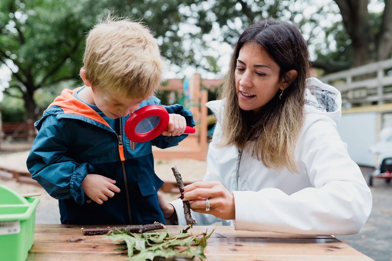 A teacher helps a student outside.
