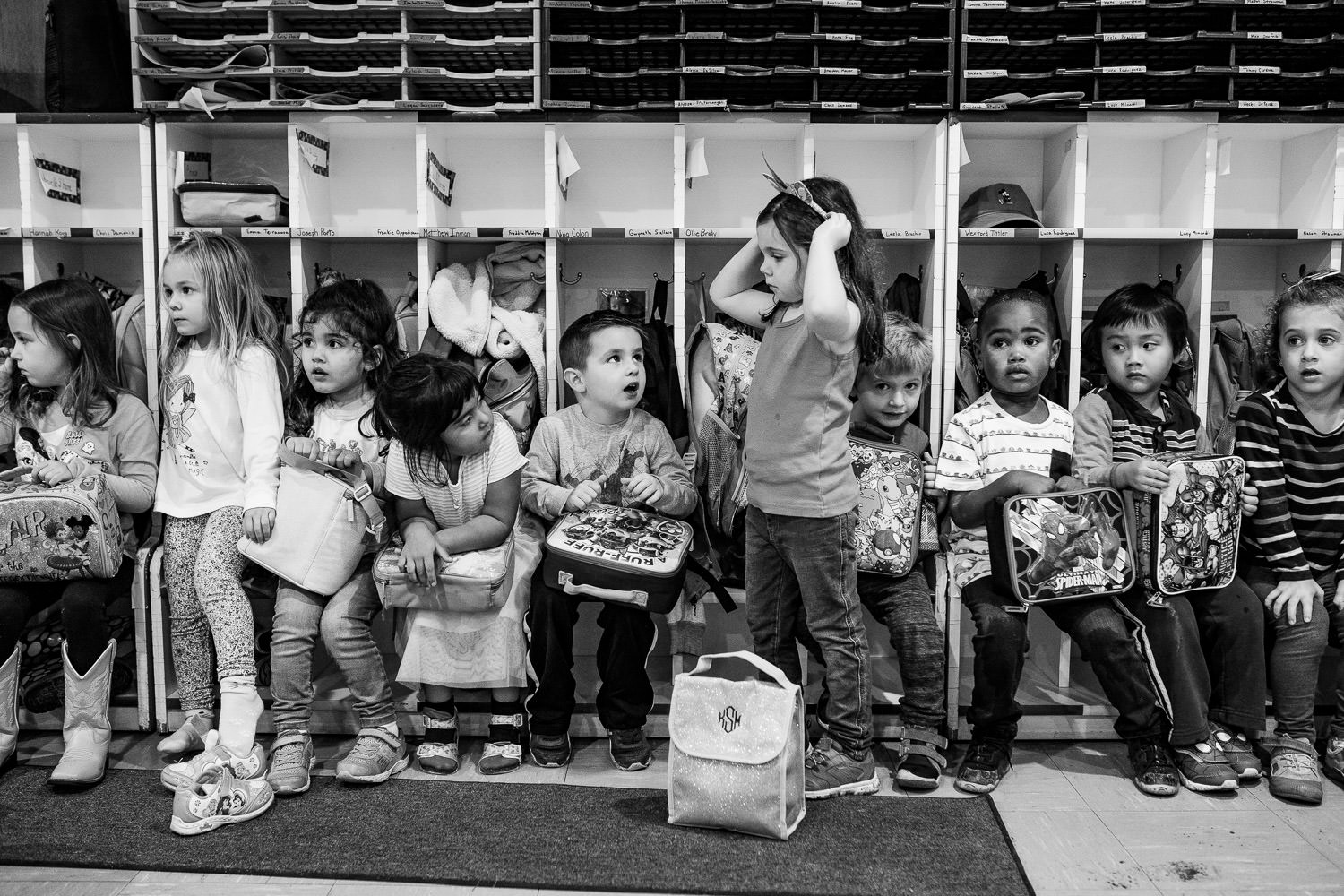 Preschoolers sit in their cubbies with their lunchboxes.