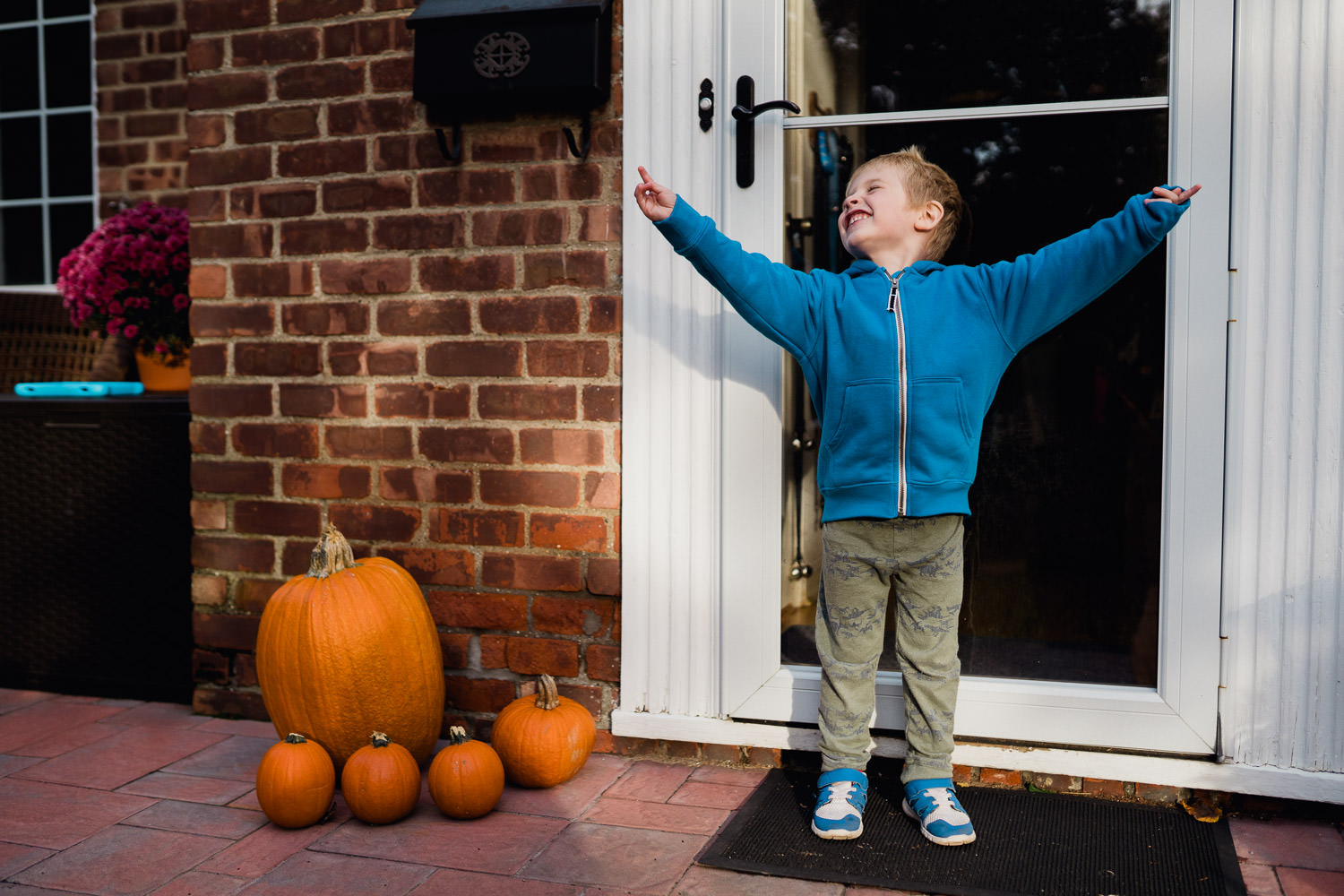A little boy cheers on his porch.