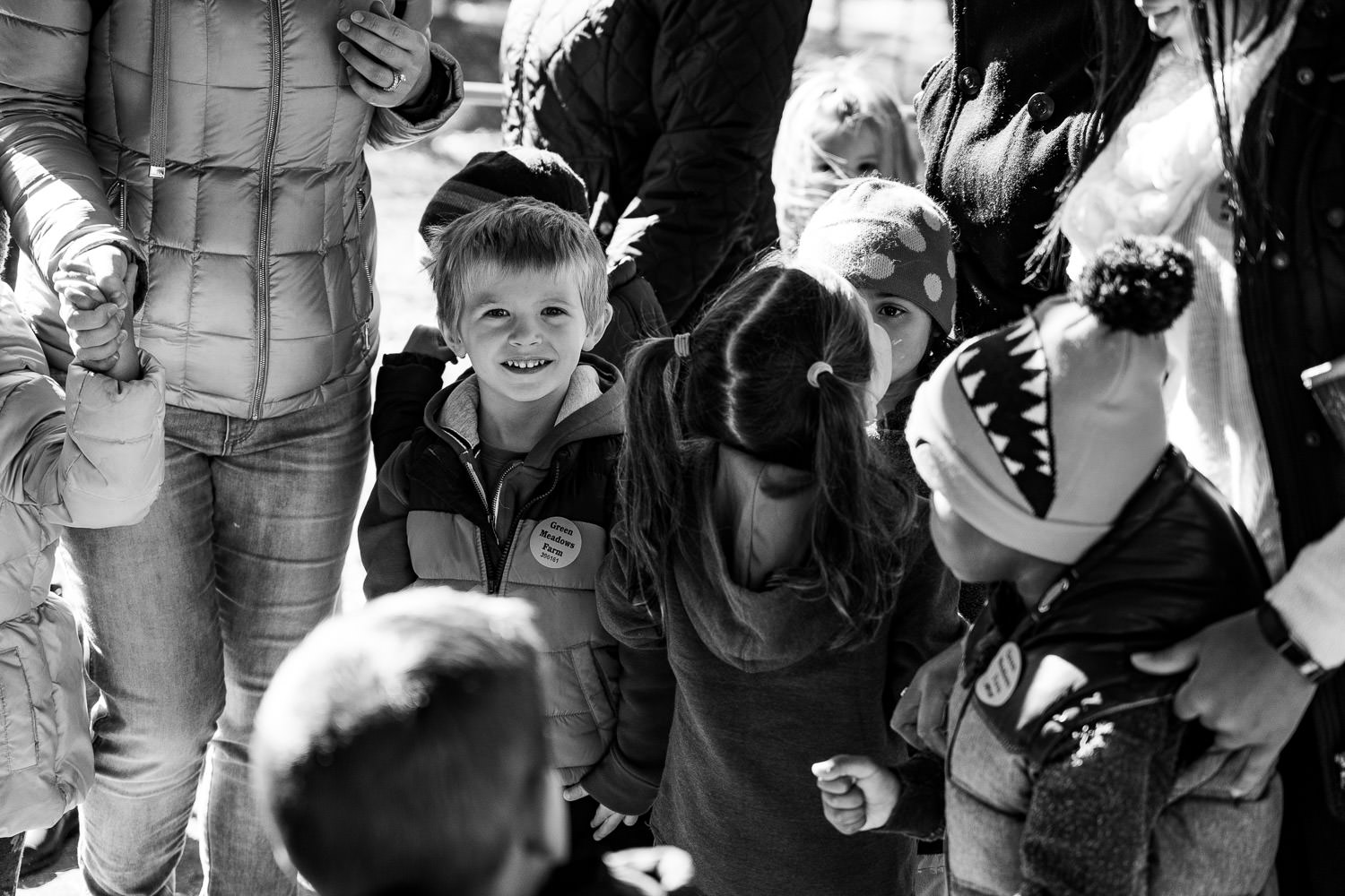 A little boy smiles in a group of his classmates.