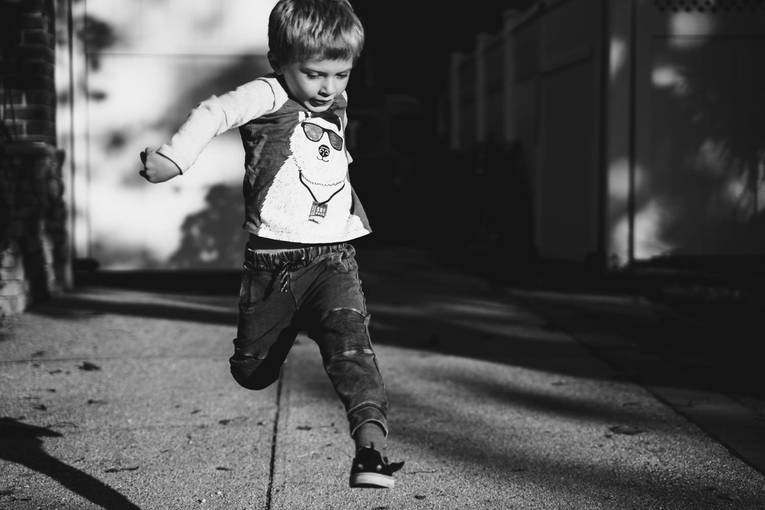 A little boy jumps in his driveway.