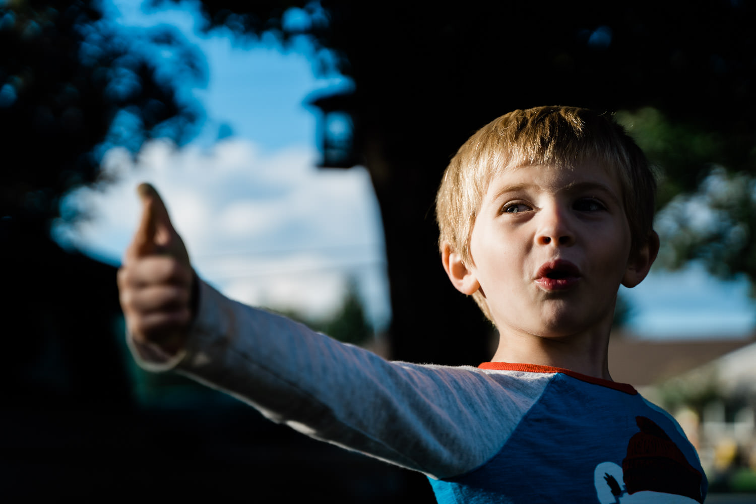 A little boy points in his front yard.
