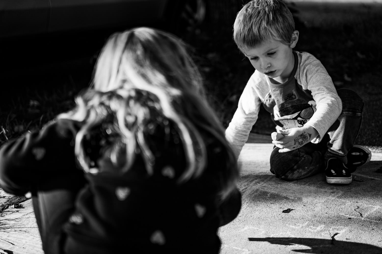 Two kids draw with chalk on the sidewalk.