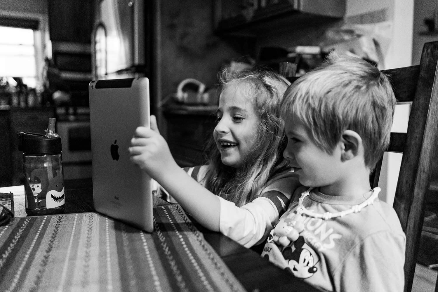 Two siblings play with a tablet at the kitchen table.