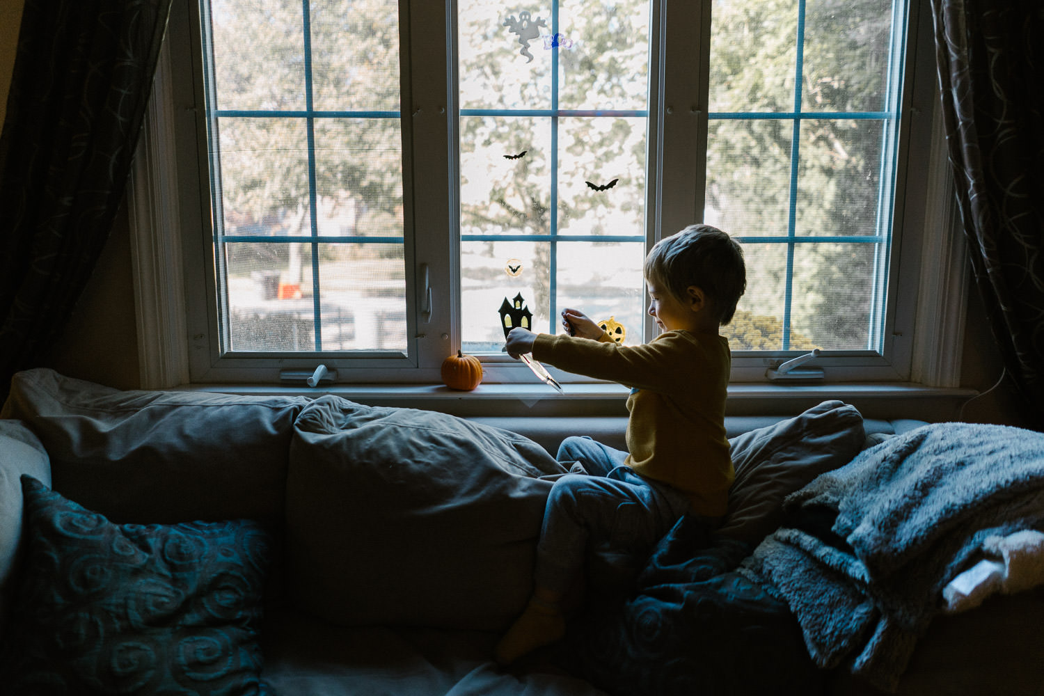 A little boy hangs Halloween gel clings on his living room windo