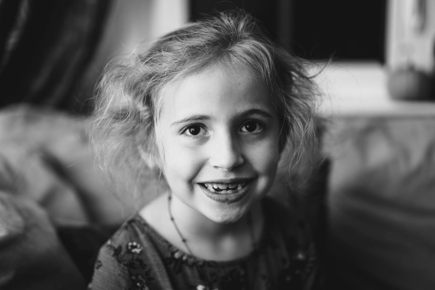 A little girl smiles at the camera.