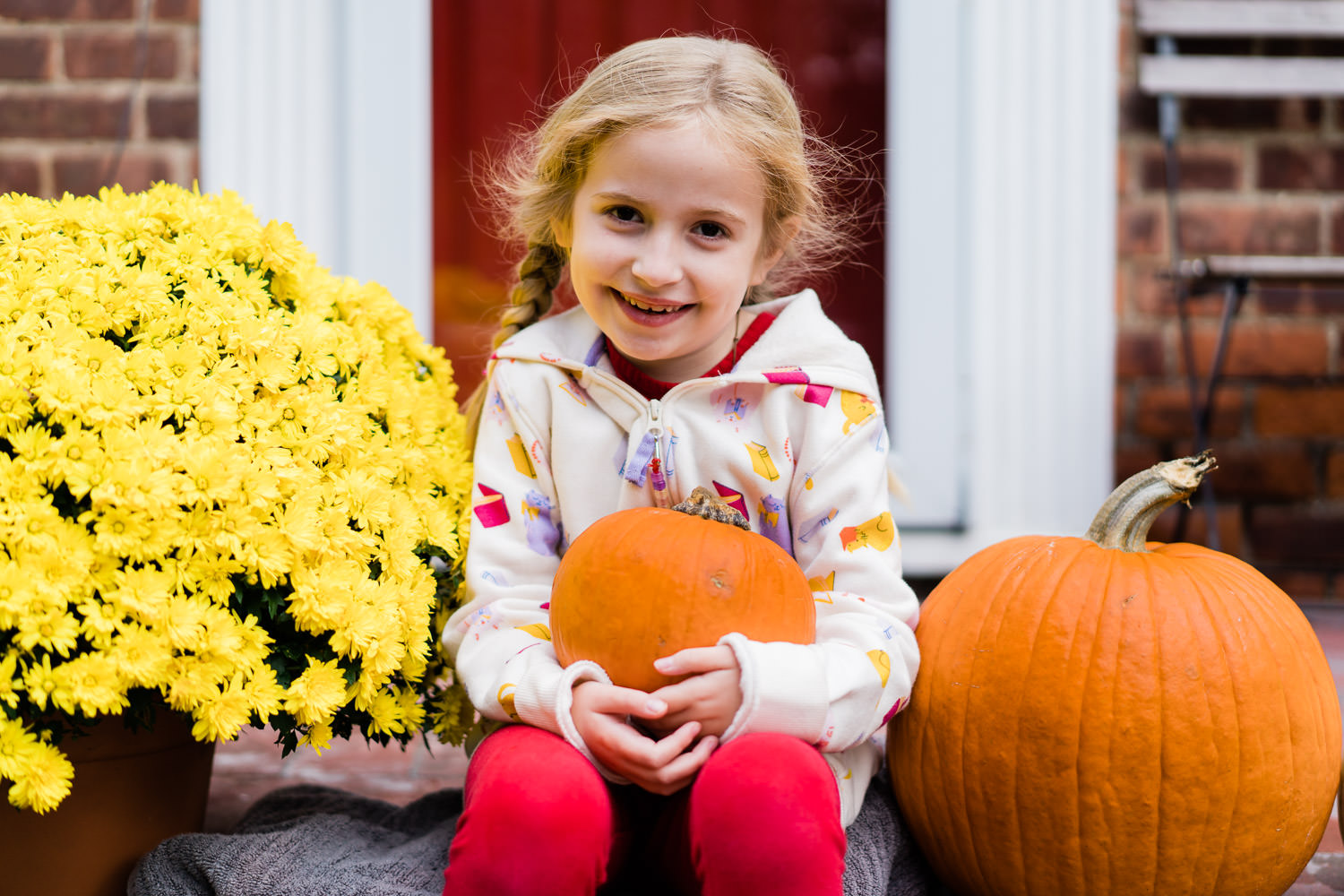 A little girl sits on her porch with some pumpkins.