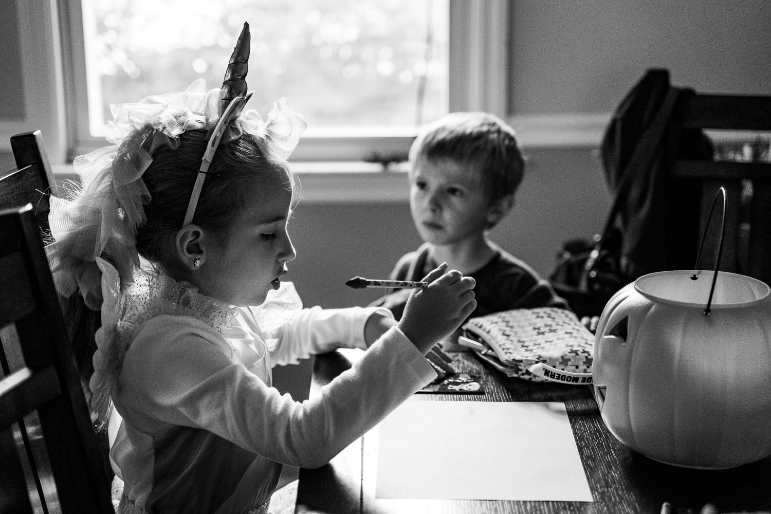 A little girl works on her homework in a unicorn costume.