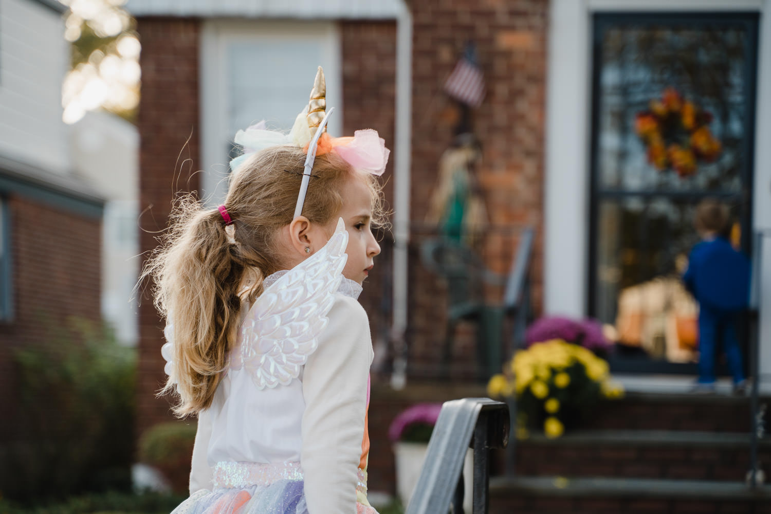 A little girl dressed as a unicorn goes trick or treating.