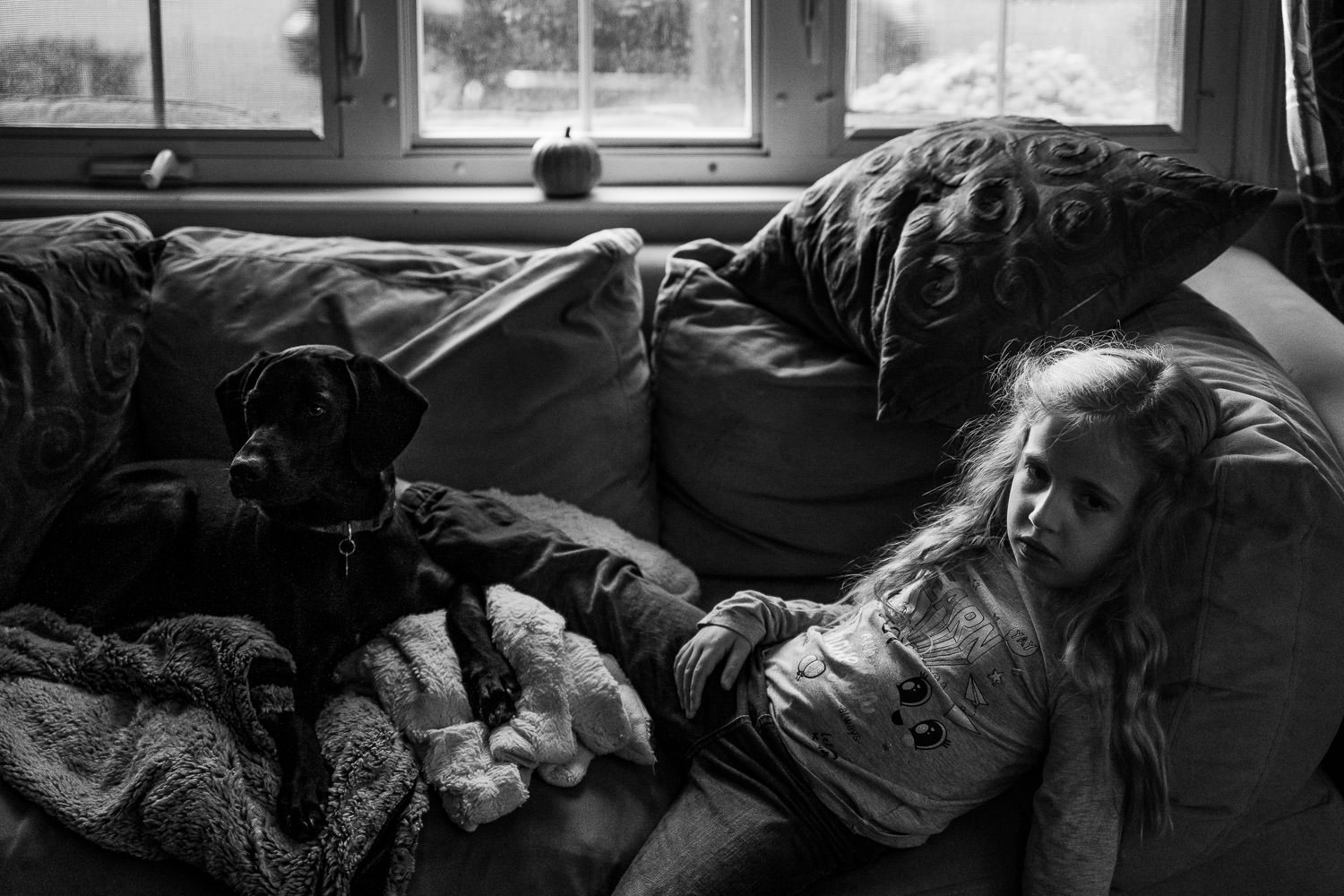 A little girl lies on the couch with her dog.