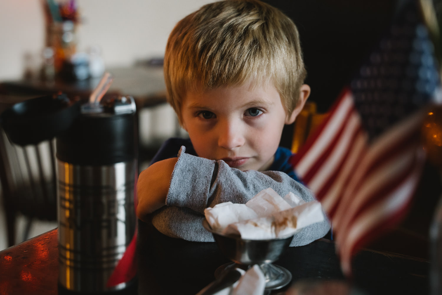 A little boy sits at a table in a restaurant.
