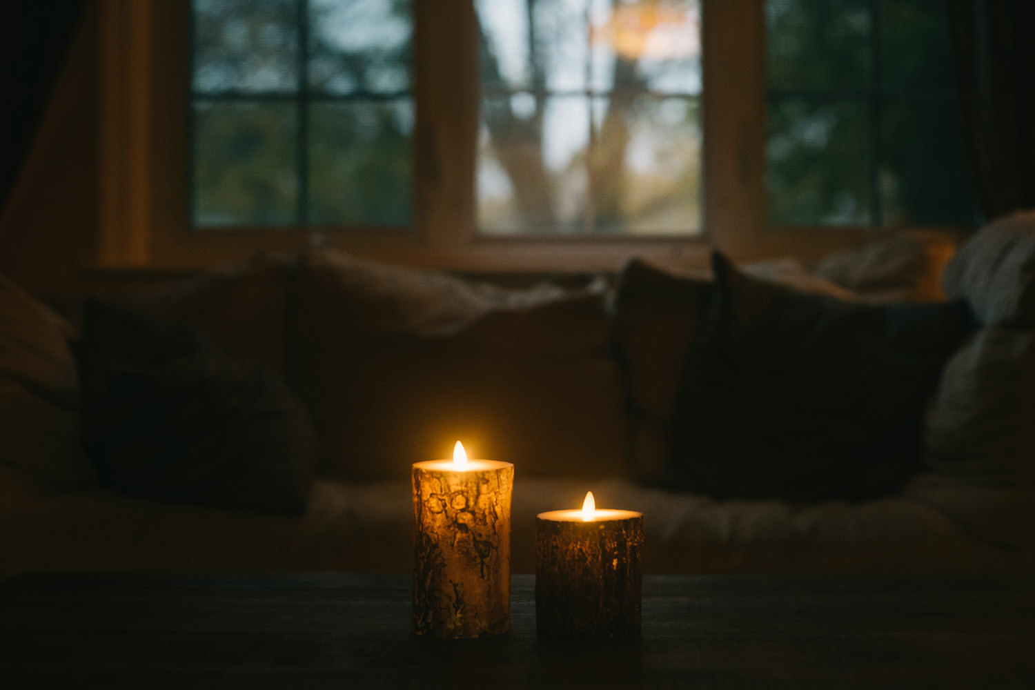 Candles burning on a coffee table.
