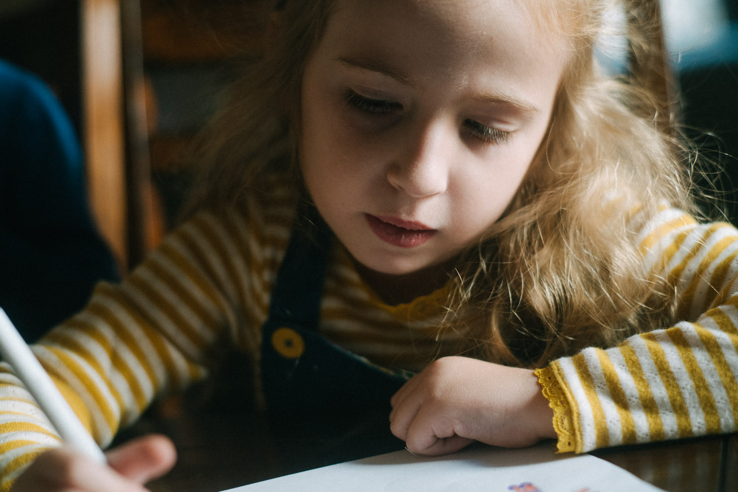 A little girl writes at her kitchen table.