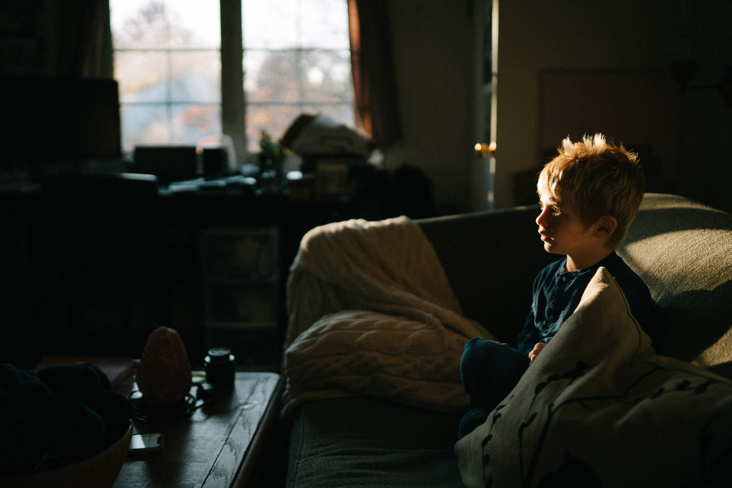 A little boy sits on a couch with golden sunlight shining on him