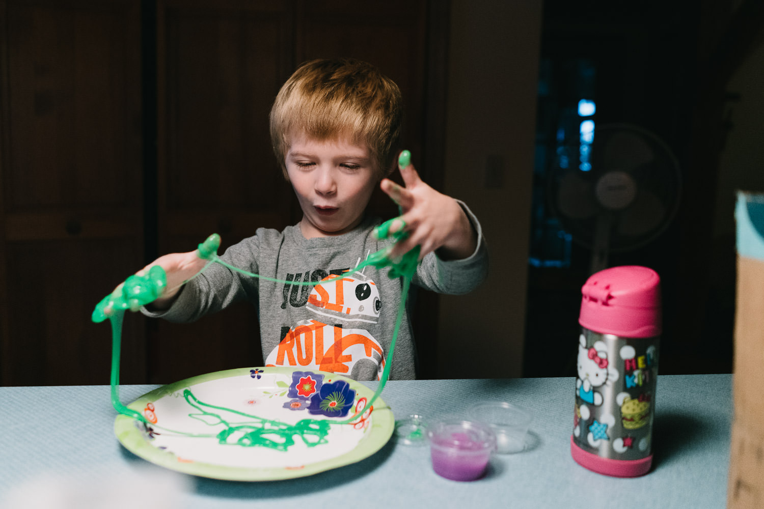 A little boy plays with green slime.