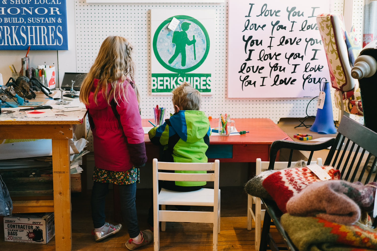 Two children draw at a table in a store in Great Barrington.