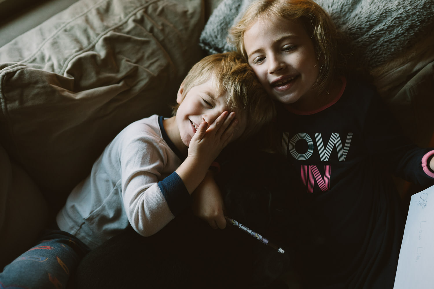 Two children snuggle on their couch.